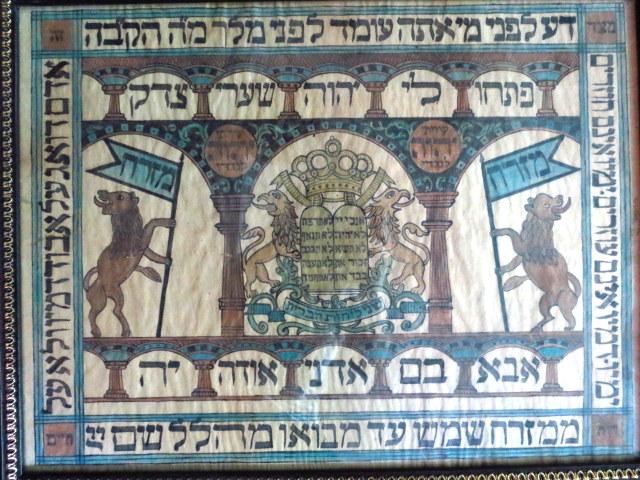 """מזרח צבעוני מצוייר ביד: במרכז זוג אריות מחזיקים את לוחות הברית, כתר תורה מעל,  כיתוב מסביב: """"דע לפני..."""""""