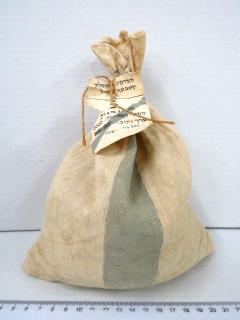 """שק בד חתום בפלומבה, המכיל 2000 מטבעות ע""""ס 5 אגורות, ס""""ה -.100 ל""""י, המדפיס הממשלתי, מטבעת ישראל Feb.6.1975"""