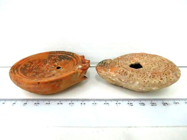 שני נרות שמן רומיים: תקופה אימפריאלית א. מאה ראשונה לספירה (חסרה פיה),  ב. עם תבליט, מאה שלישית לספירה