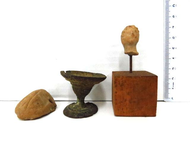 שלושה פריטים רומיים: ראש פיגורת טרה קוטה, צלמית קיסרית, מאות 2-3 לספירה, ידית נר טרה קוטה, בסיס גביע (קלוס) עשוי ברונזה, המאה השניה לספירה