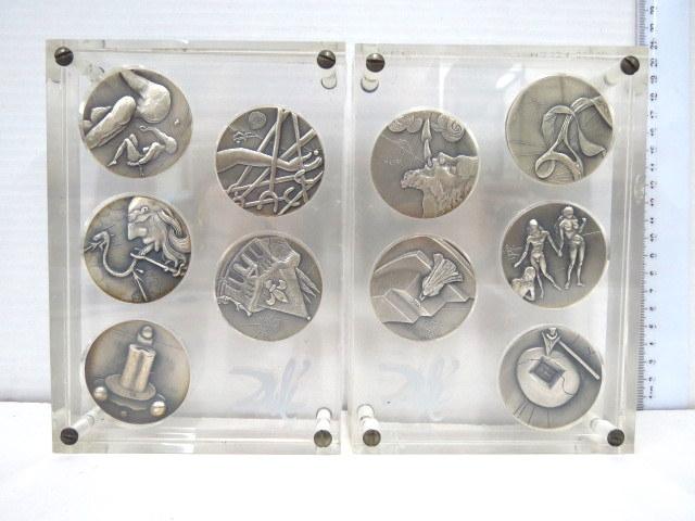 """עשר מדליות כסף (999), סידרת עשרת הדיברות 1975, כ-51 גרם כ""""א, חתומים בלוח, בשתי קופסאות פרספקס מקוריות עם הטבעת חתימת האמן"""