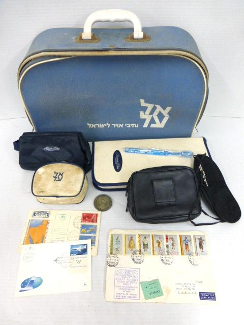 """לוט של כ-20 פריטי אל-על הכולל: מזוודה, שלושה תיקי Business Class, שני כיסויי עינים וכו', שלוש מעטפות """"טיסה ראשונה"""",אל-על , ומדליה מצופה כסף לכב' הטיסה הטרנסאטלנטית הראשונה 25.12.57"""