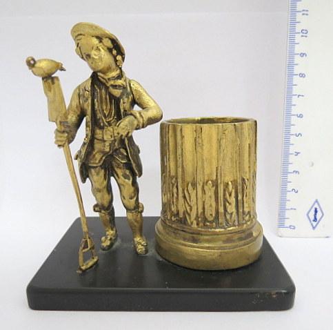 מחזיק לגפרורים, ברונזה מוזהבת על בסיס אוניקס, צורת נער עם עט ויונה וכן עמוד