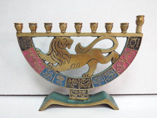 חנוכית פליז לנרות, צורת מנורה בסיס עם דוגמת אריה ושנים עשר שבטי ישראל, תוצ' תמר, 1967, איכות יצוא (במקור עיצוב של דייגי)