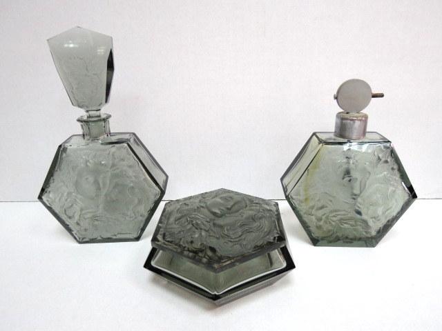 שני בקבוקי בושם וקופסה אר דקו: מפזר בושם בקבוק עם פקק וקופסה לפודרה, עליהם תבליט פני גבר ואישה, , זכוכית גוון אפור