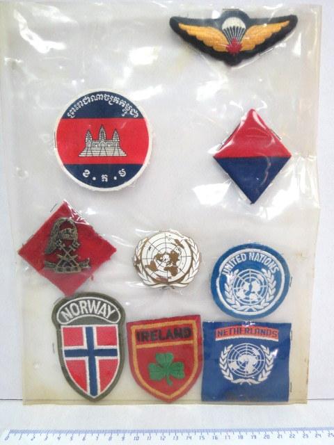 """לוט תשעה סמלים, תגים של יחידות או""""מ ששירתו באזור תאילנד: סמל כומתה, ותג, תגים שלהולנד, אירלנד, ונורווגיה, תג וסמל כומתה כללי, כנפי צניחה קנדה ונוסף"""
