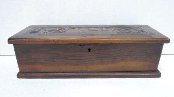 """קופסת עץ זית מאורכת, עם גילוף על המכסה, מראה בתים בירושלים העתיקה, תחילת המאה ה20, 26X9X7.5 ס""""מ"""