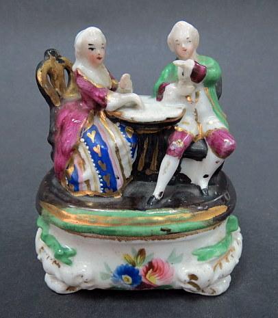 קסת דיו מפורצלן, המכסה צורת בני אצולה יושבים ליד שולחן עם כלי לחול, הכלי לדיו חסר (שחזור גס)