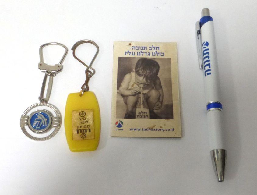 ארבעה פריטי תנובה: עט, שני מחזיקי מפתחות ומגנט למקרר