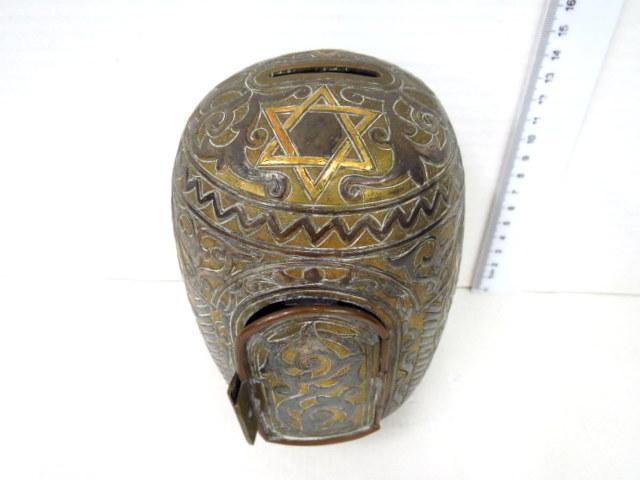 """קופת צדקה, פליז עם אינליי כסף עבודת דמשק, עם מראה מנורות וכיתוב: """"גדול המלוה יותר מן העושה צדקה"""""""