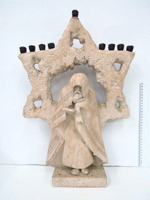 חנוכית קרמיקה גדולה לנרות הבזיכים ממתכת, במרכז החנוכיה יהודי בתפילה ומאחוריו מגן דוד