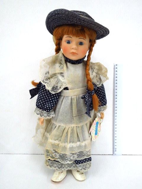 ילדה בשמלה עם כובע קש וצמות ג'ינג'יות