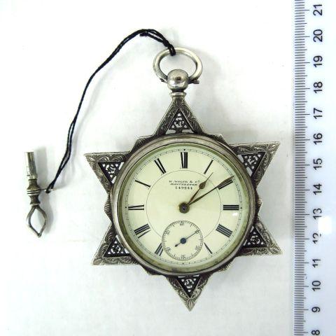 """הקופסה כסף שנת 1880, עם מסגרת צורת מגן דוד, וכיתוב """"חי """" בכל ששת הפינות, מחוג שניות נפרד, מתיחה בעזרת מפתח, מנגנון טעון תיקון"""