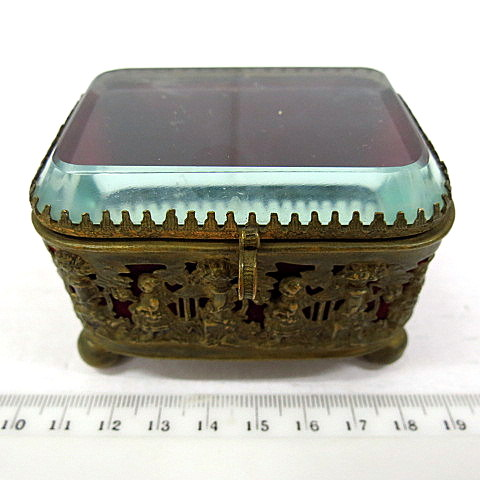 קופסת תכשיטים קטנה עשויה פליז רקוע, עם עבודת תבליט, מכסה לוח קריסטל, חתום 1859 La Ruginsa