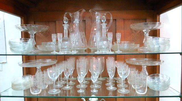 """מע' כוסות זכוכית מלוטשות כולל: שני קנקני מים, שני בקבוקי ליקר, שתי צלחות עוגה על רגלית כ""""א,  שתי קעריות, כ""""א על רגלית, שבעה גביעים גדולים, שבעה ג"""