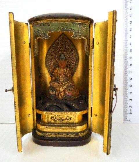 """מקדש ביתי יפני, בודהא בתנוחת ישיבה על אריה מיתולוגי ובסיס סלעי על פודיום מפואר, תחילת המאה ה20, בקופסה לנשיאה, פנים מוזהב, גובה 13.5 ס""""מ"""